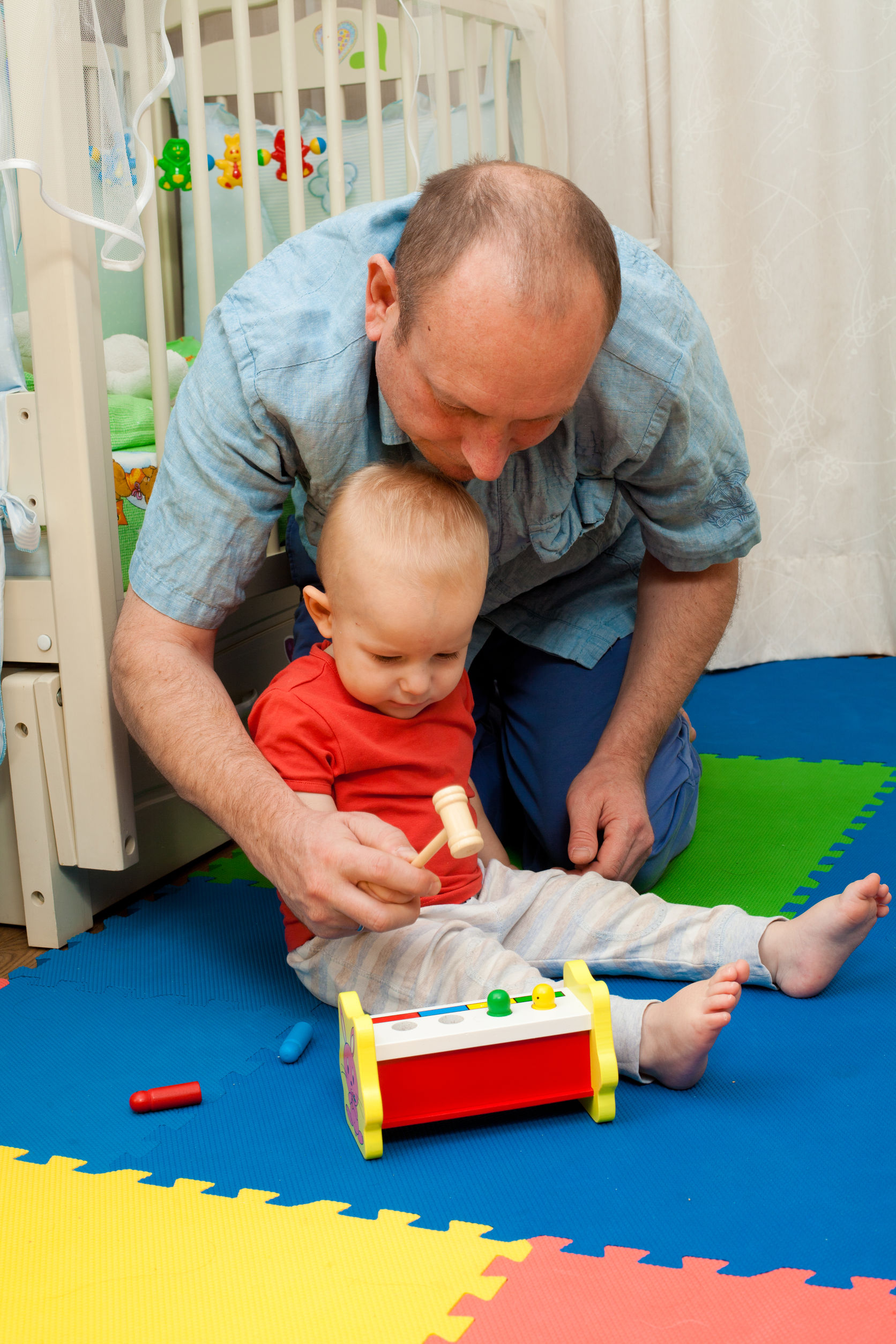 Vater spielt mit Baby ein Hammerspiel
