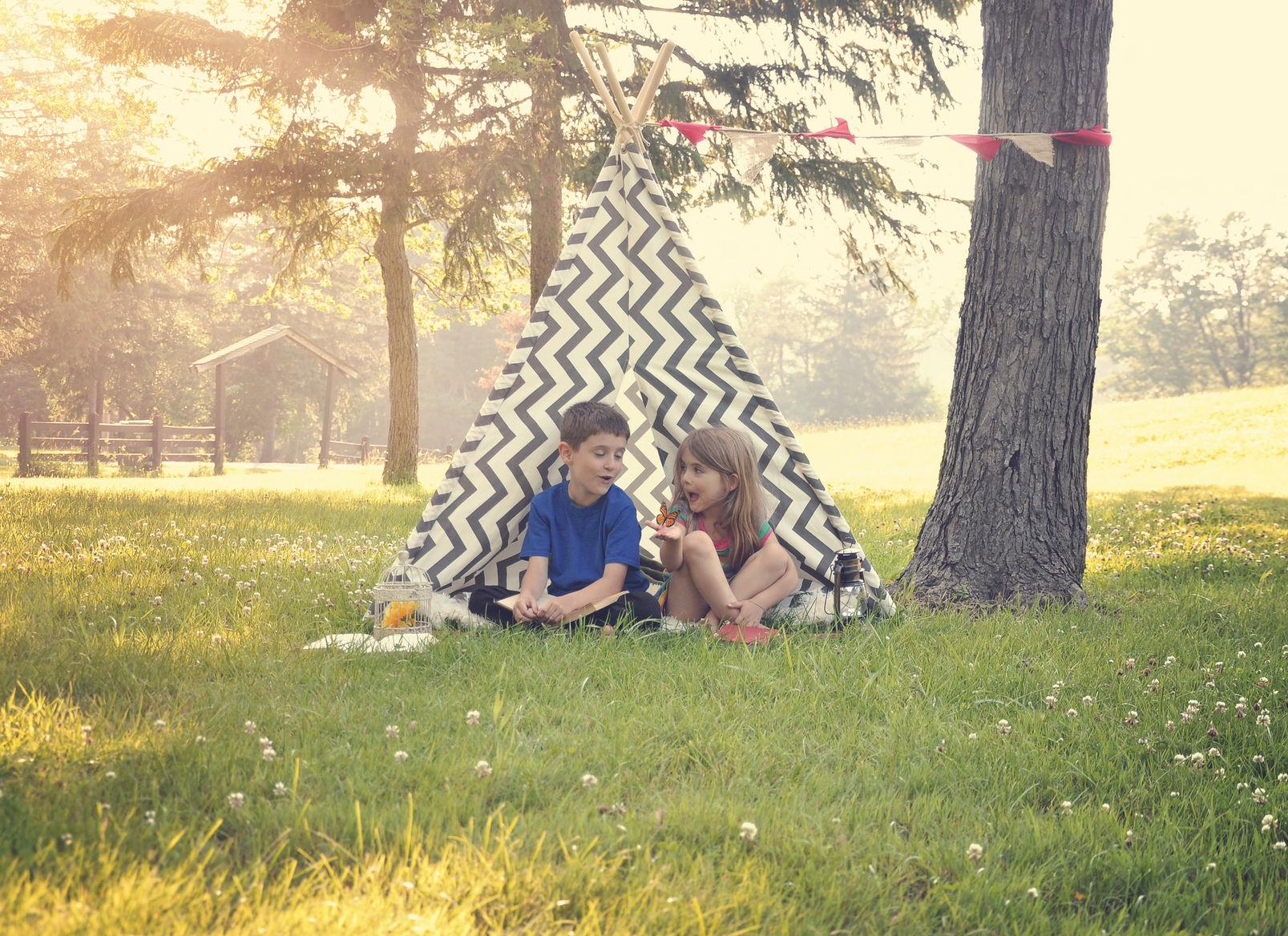 Zwei Kinder sitzen im Indianerzelt auf einer Wiese