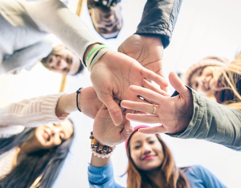 Jugendliche halten alle ihre Hände gemeinsam in die Mitte