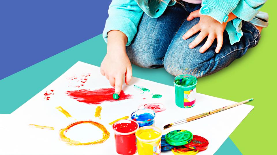 Kind malt mit Fingerfarbe auf einem Blatt Papier