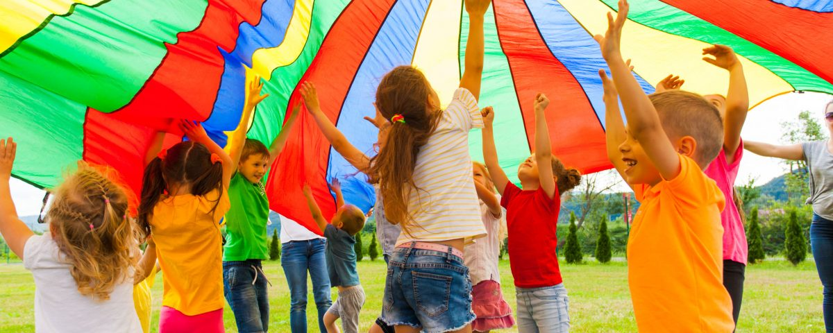 Joyous classmates jumping under colorful parachute in the summer outdoors